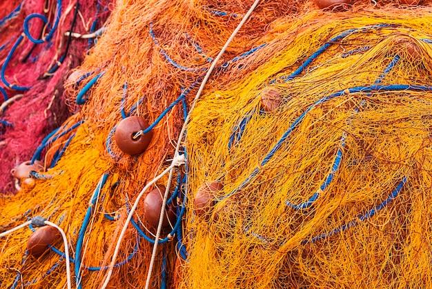 Rete da pesca di corde arancioni e gialle e pila di boe sul molo.