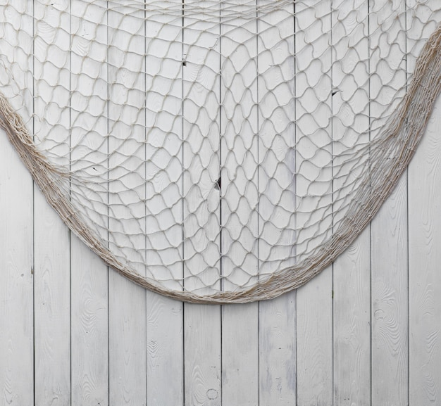 Rete da pesca su uno sfondo di legno biancosfondo per testo o immagine