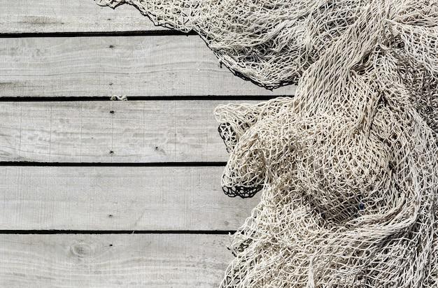 Rete da pesca sul piano di calpestio in legno dello sfondo del molo con spazio di copia