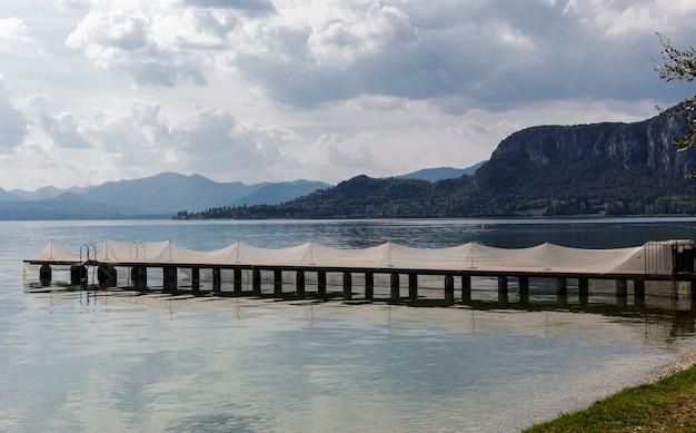Reti da pesca stese su un molo sul lago di garda.