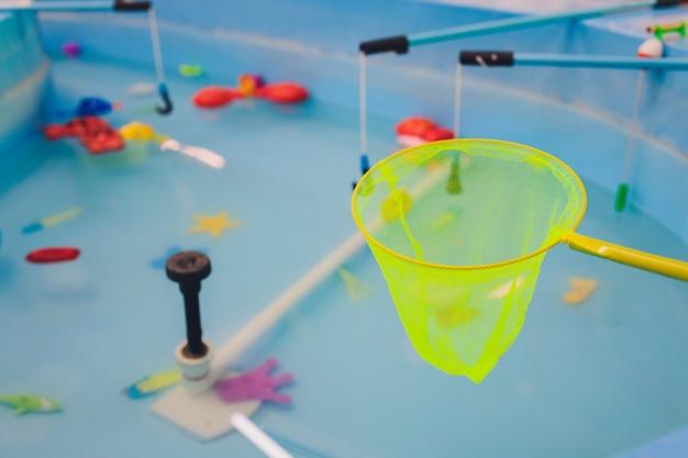 Pesca nella piscina per bambini. giocattoli per bambini in piscina. canna da pesca per pesci giocattolo. bambini allegri che pescano, pescano nella piscina per bambini.
