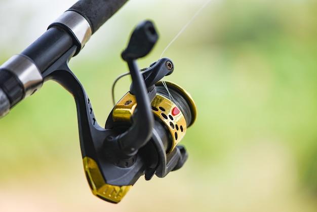 Mulinello da pesca sulla canna da pesca, pesca sull'alimentatore con lo sfondo della natura