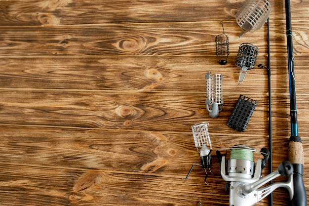 Canna da pesca con accessori sulla tavola di legno