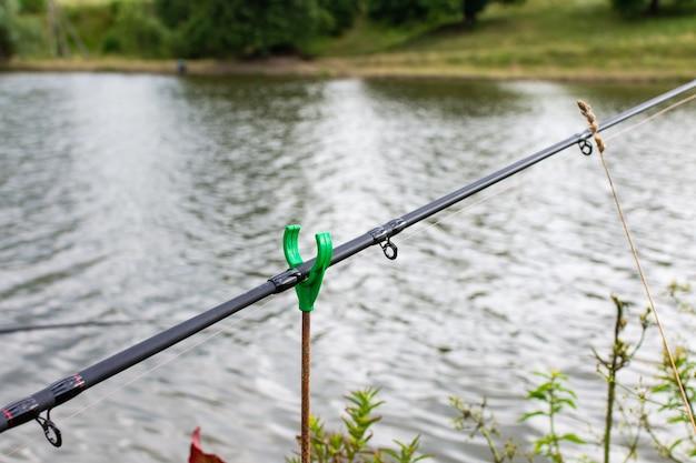 Canna da pesca con campana in acqua, pesca in estate