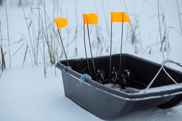 Slitta da pesca con attrezzatura su un lago innevato