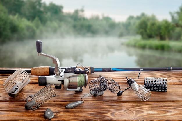 Attrezzatura da pesca e accessori sul tavolo contro il lago