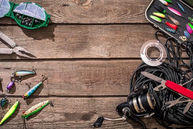 Attrezzatura da pesca - pesca a spinning, lenza, ganci ed esche su fondo in legno. vista dall'alto. copia spazio. natura morta
