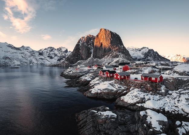 Villaggio di pescatori con montagne rocciose sulla costa ad alba alle isole lofoten, norvegia