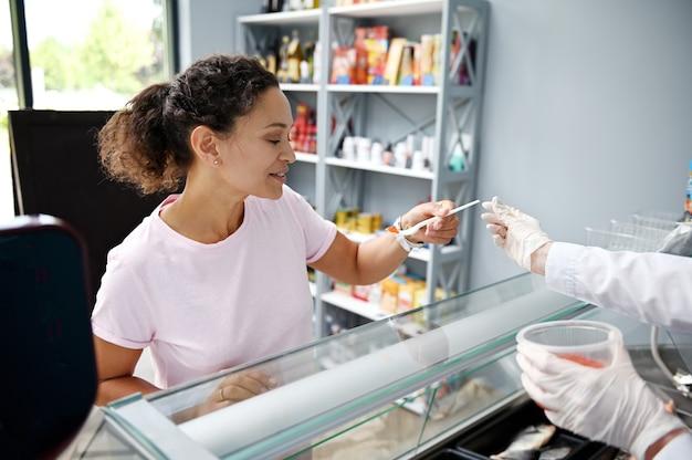 Pescheria che serve il cliente del negozio di pesce. donna di razza mista, acquirente che assaggia il caviale al negozio di frutti di mare. vendita al dettaglio di frutti di mare. consumismo. cibo e bevande.