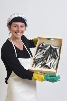Un pescivendolo con una scatola di sardine su sfondo bianco