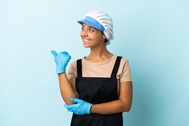 Donna asiatica fishwife che punta al lato per presentare un prodotto