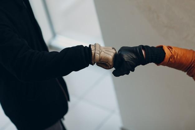 Pugno di mano in guanto che urta saluto di sicurezza della pandemia di coronavirus covid-19. nuova normalità.