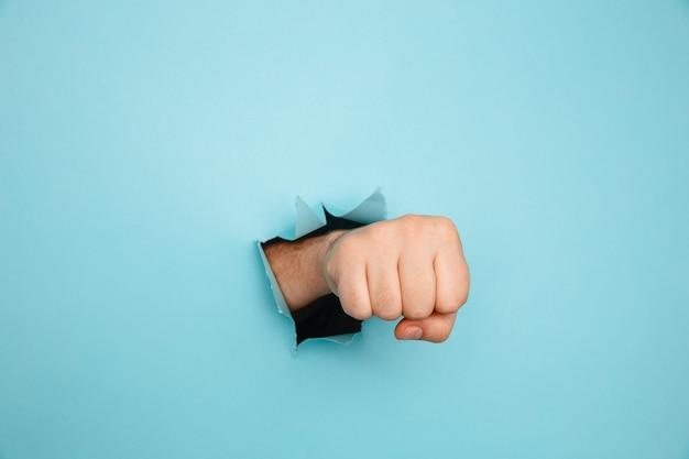 Pugno che perfora attraverso il muro di carta blu. minaccia, lotta e sport da combattimento. spingi attraverso il muro