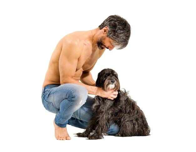 Uomo in forma atletico a torso nudo sulla cinquantina che si china ad accarezzare il suo cane
