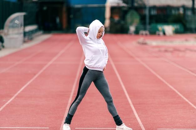 Montare bella donna sportiva con felpa con cappuccio su facendo esercizi di riscaldamento in pista. lunghezza intera.