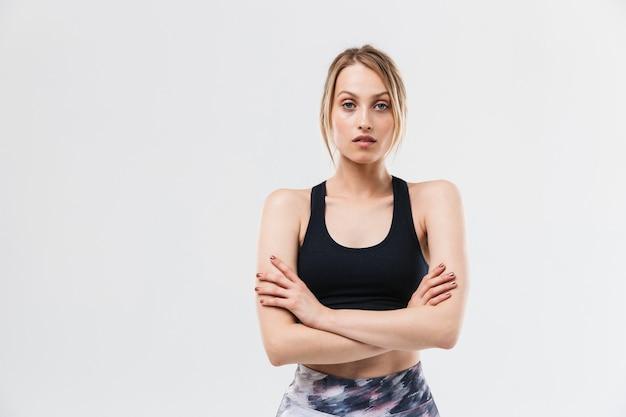 Fit donna bionda vestita di abbigliamento sportivo che si allena e fa esercizi durante il fitness in palestra isolato su muro bianco