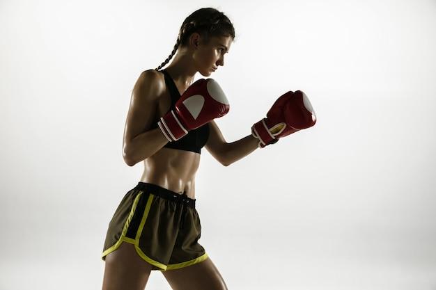 Montare la donna caucasica nella boxe degli abiti sportivi isolata sul muro bianco. pugile caucasico femminile alle prime armi che si allena e si esercita in movimento e azione. sport, stile di vita sano, concetto di movimento.