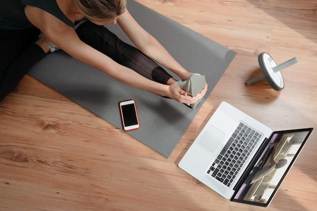 Montare la femmina europea che pratica yoga o pilates al chiuso sul tappetino, facendo esercizi e stretching