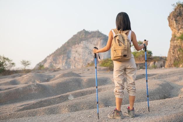 Montare l'escursionista femminile con zaino e pali in piedi sul crinale della montagna rocciosa che guarda valli e vette.