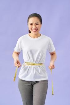 Ragazza fitness in forma che misura la sua vita con metro a nastro su viola