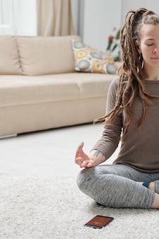 Montare la ragazza in activewear seduta sul pavimento con le gambe incrociate e le mani sulle ginocchia mentre si pratica yoga