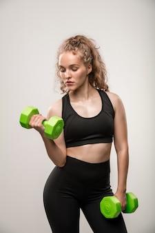 Ragazza in forma in abbigliamento sportivo nero che tiene in mano manubri verdi mentre piega un braccio durante l'esercizio fisico su grigio