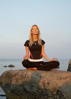 Ragazza adatta che medita in riva al mare