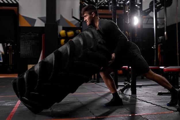 Montare atleta maschio facendo esercizio di ribaltamento dei pneumatici al chiuso nella moderna palestra. cross fit e allenamento. atleta forte e bello in abbigliamento sportivo. sport, stile di vita sano