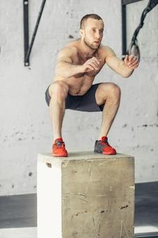 Uomo adatto che fa i salti della scatola in una palestra