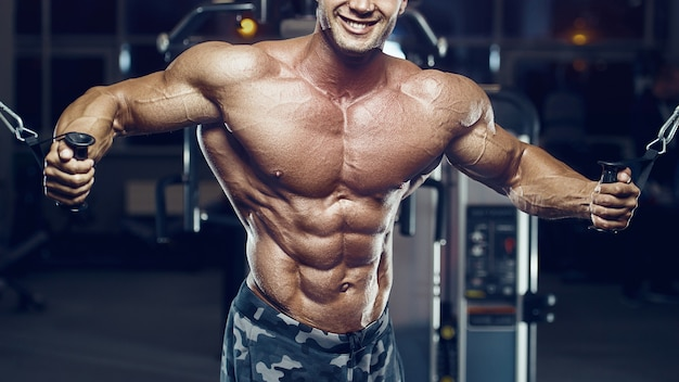 Uomo adatto che fa crossover del cavo. allenamento dei muscoli pettorali in palestra. esercizio di pompaggio del torace