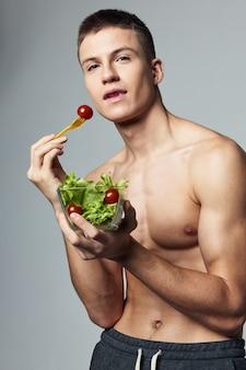 Uomo adatto che mangia un'insalata