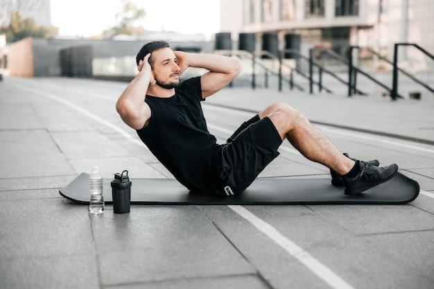Montare la pressa di pompaggio dell'uomo sdraiato sul tappetino yoga nero