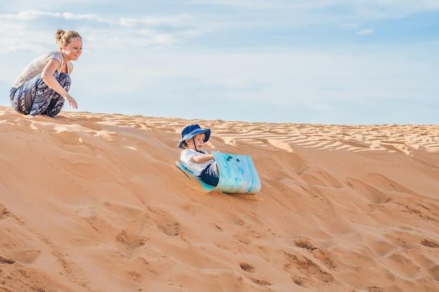 Montare la madre con il figlio che corre nel deserto di gran canaria, maspalomas al tramonto.