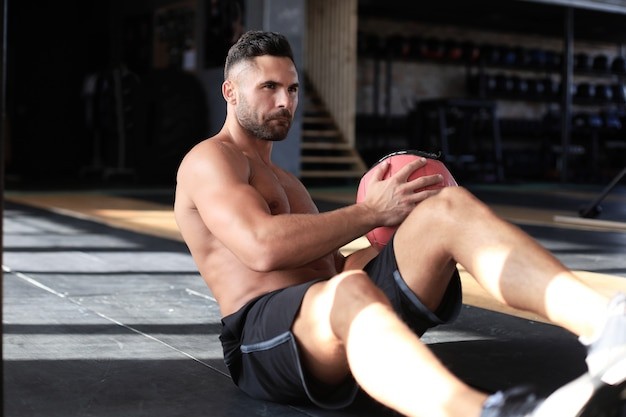 Uomo in forma e muscoloso che si esercita con la palla medica in palestra.
