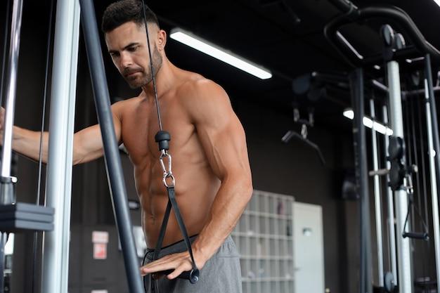 Uomo in forma e muscoloso allena i muscoli pettorali su un simulatore di blocchi in palestra.