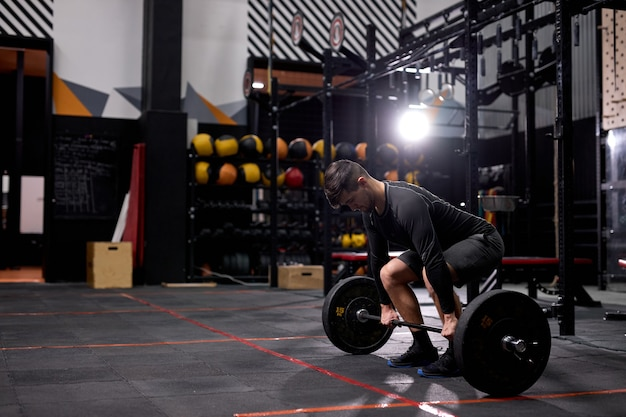 Fit uomo muscoloso con grandi muscoli che tengono un peso elevato per cross fit swing training hard core allenamento in palestra, indossando abiti sportivi, da solo. ritratto