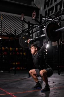 Uomo muscoloso in forma con grandi muscoli che tengono un peso elevato per cross fit swing training hard core workout in palestra, indossando abiti sportivi, da solo. ritratto