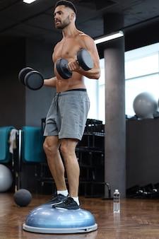 Uomo in forma e muscoloso che si allena con i bumbbells sulla palla bosu dell'emisfero ginnico in palestra.