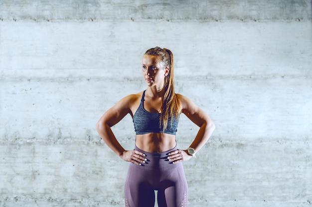 In forma bruna sportiva muscolare in abiti sportivi in piedi con le mani sui fianchi e distogliere lo sguardo