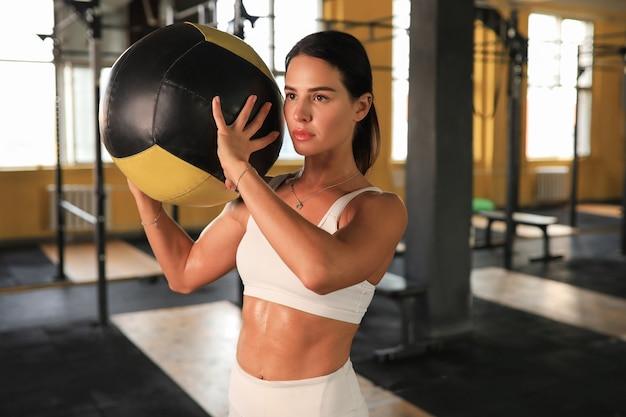 Donna in forma e muscolare che si esercita con la palla medica in palestra.
