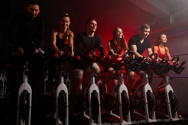 Montare le persone che guidano insieme le cyclette durante una sessione di allenamento cardio in palestra, concentrandosi sull'allenamento in attesa