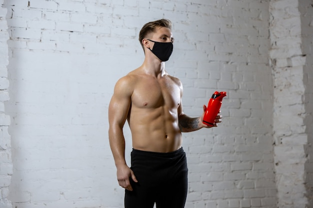 In forma. atleta professionista maschio formazione su sfondo muro di mattoni indossando maschera facciale. sport durante la quarantena della pandemia mondiale di coronavirus. giovane che pratica in palestra utilizzando attrezzature sicure.