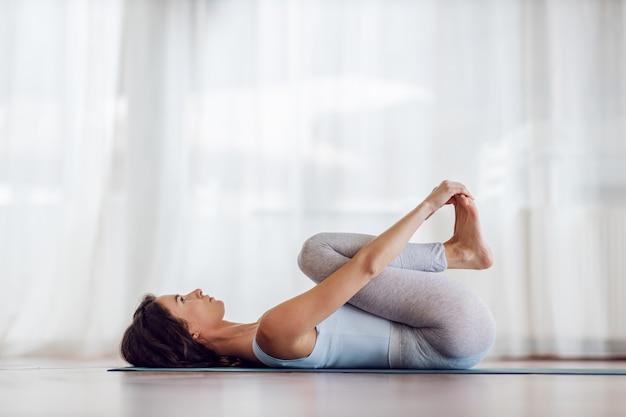 Ragazza adatta dello yogi sottile nella posa di yoga del bambino felice. interiore dello studio di yoga.