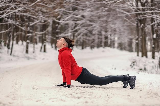 Sportivo in forma che fa yoga nella foresta al giorno di inverno nevoso. stile di vita sano, fitness invernale