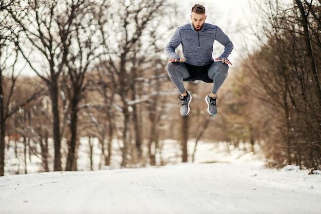 Sportivo in forma che salta in alto nella foresta e facendo esercizi di fitness in una giornata invernale nevosa.