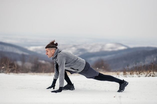 Montare lo sportivo nella posizione di partenza. sportivo facendo esercizi con tempo nevoso in natura. natura, fitness all'aperto, fitness invernale