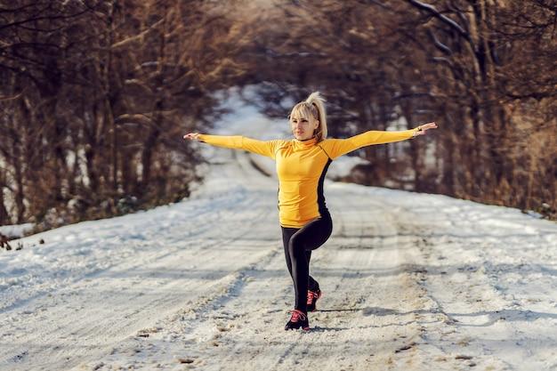 Montare sportiva facendo affondi sul sentiero innevato al giorno di sole invernale. esercizi di riscaldamento, fitness invernale, sane abitudini