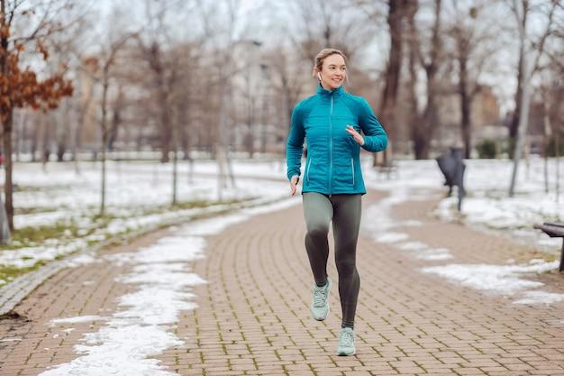 Sportiva in forma jogging sul percorso nel parco il giorno di inverno nevoso.