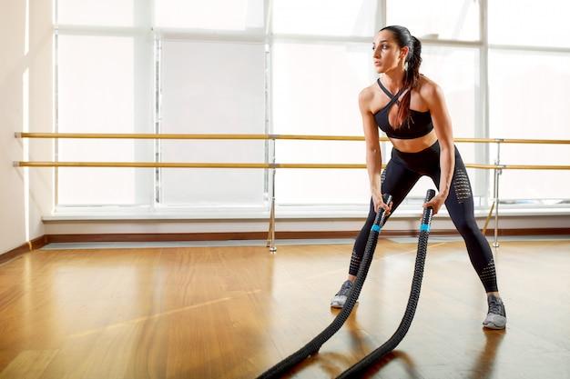 Sportiva adatta, sportiva e atletica che lavora in una palestra. addestramento della donna usando le corde di battaglia. concetto di sport, atletica e fitness.