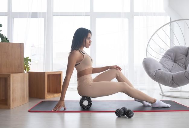Fit sportivo da donna di colore che indossa abbigliamento sportivo roll on foam massaggio miofasciale rullo massaggiando i muscoli sul pavimento della stuoia di yoga a casa